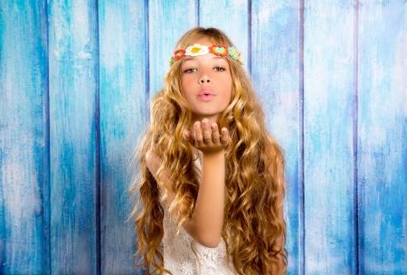 Blonde hippie kinderen meisjes blazende mond met de hand op blauwe grunge hout
