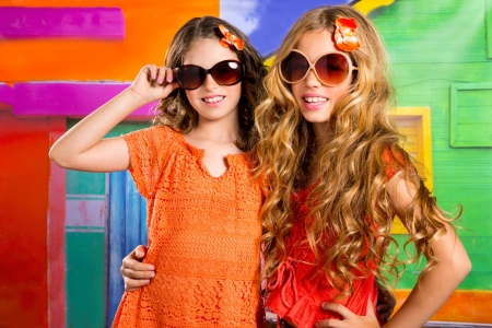 children friends girls with fashion sunglasses in vacation at tropical colorful house photo