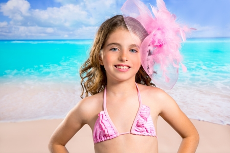 Children girl in tropical turquoise beach vacations with pink fashion style photo