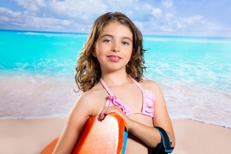 Children fashion surfer girl in tropical turquoise beach vacation smiling photo