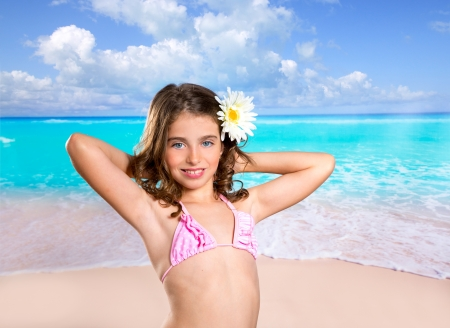 Brunette girl in tropical beach with daisy flower happy for vacation photo
