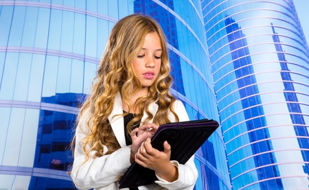 buidings: Children business student girl with tablet pc on urban blue buidings background