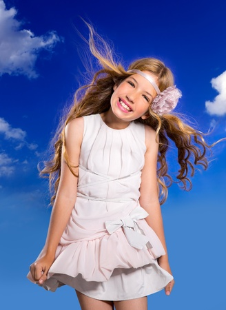 dress blowing in the wind: Blond happy girl with fashion dress and wind blowing hair in a blue sky background
