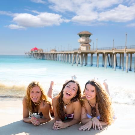 brunette teen: happy three teen friends girls lying on beach sand smiling at Huntington Beach California Stock Photo