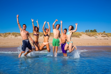 Happy excited teen boys and girls group jumping at the beach splashing water Stock Photo