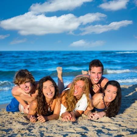 petite fille maillot de bain: Les filles du groupe de l'adolescence les gar�ons et s'amuser heureux sur la plage de sable bleu