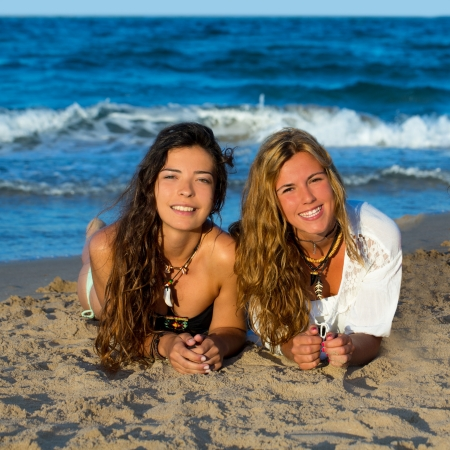 hot girl lying: Girls friends having fun happy lying on the beach sand shore