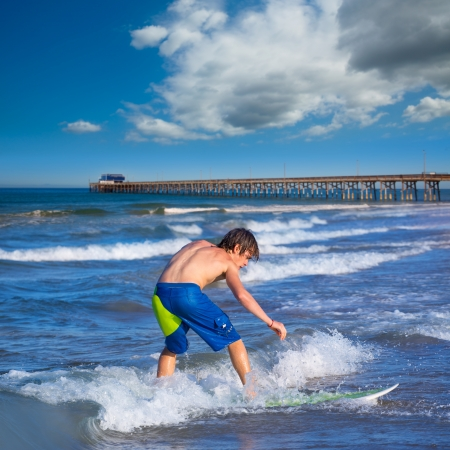 watersports: Boy surfer surfing waves on Newport pier beach  California