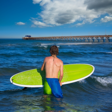 boy surfer waiting for the waves on Newport pier beach California photo