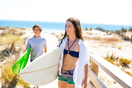 Teenager surfers walking to the beach in sunny summer day photo