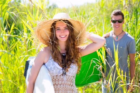 Girl surfer with beach hat walking with surfboard and her friend photo