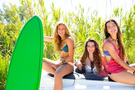 teen beach: surfer beautiful girls group holding happy surfboards on convertible car