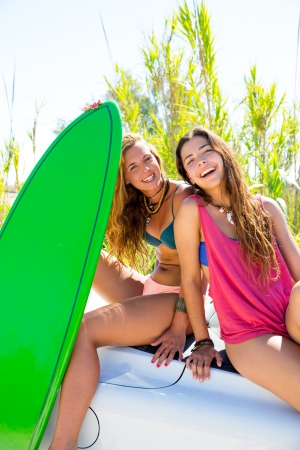 Happy crazy teen surfer girls smiling on white convertible car photo