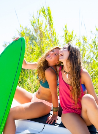 teen bikini: Happy crazy teen surfer girls smiling on white convertible car Stock Photo
