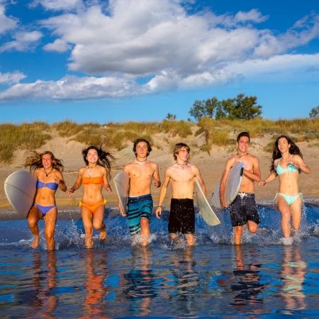 mojada: Surfistas adolescentes varones y el grupo de niñas corriendo feliz de la playa que salpica el agua