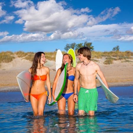 blond boy: Happy beautiful teen surfers talking on beach shore smiling Stock Photo