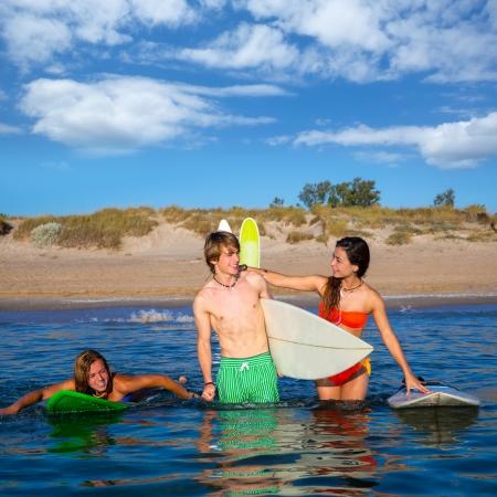 Happy beautiful teen surfers talking on beach shore smiling photo