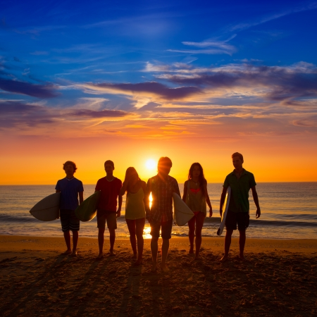 backlights: Surfers teen boys and girls group walking on beach at sunshine sunset backlight