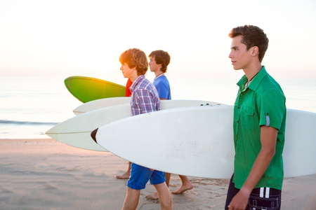 Surfer teen boys group walking at beach shore on sunshine or sunset photo