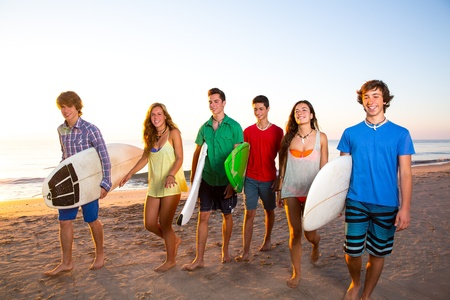 Surfer teen boys girls group walking on beach at sunshine sunset photo