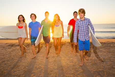 Surfers teen boys and girls group walking on beach at sunshine sunset backlight photo