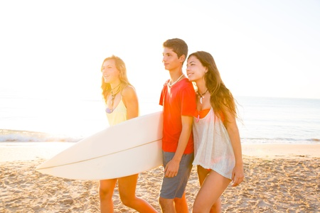 Surfer girls with teen boy walking on beach shore high key photo