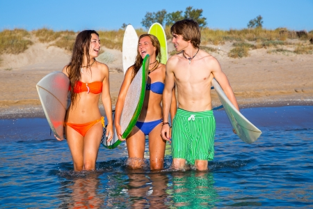 Happy beautiful teen surfers talking on beach shore smiling photo