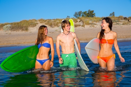 Happy beautiful teen surfers talking on beach shore smiling Stock Photo - 21926499