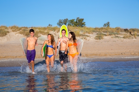 surfer teenagers boys and girls group running happy to the beach splashing water photo