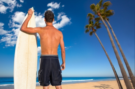 man behind: Boy surfer back rear view holding surfboard on California palm trees beach Stock Photo