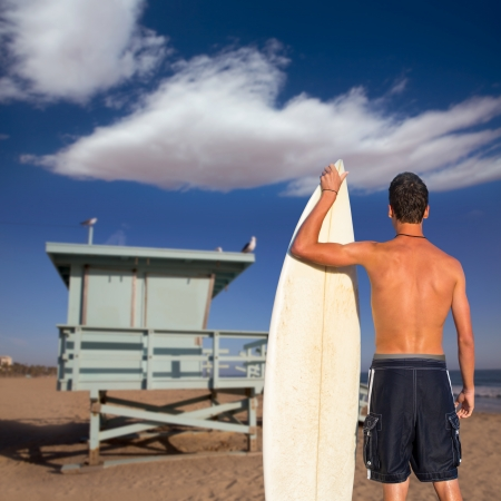 Boy surfer back rear view holding surfboard on santa Monica Lifeguard house California photo