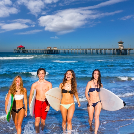 boys and girls teen surfers coming out from the Huntington beach California photo