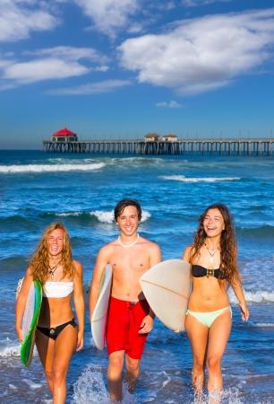 huntington beach: boys and girls teen surfers coming out from the Huntington beach California Stock Photo