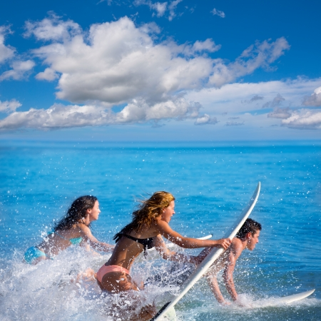 Boys and girls teen surfers running jumping on surfboards at the beach photo