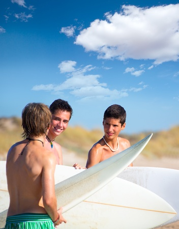 Surfer teen boys talking on beach shore holding surfboards photo