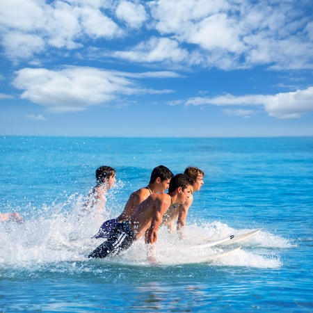 Boys teen surfers surfing running jumping on surfboards at the beach photo