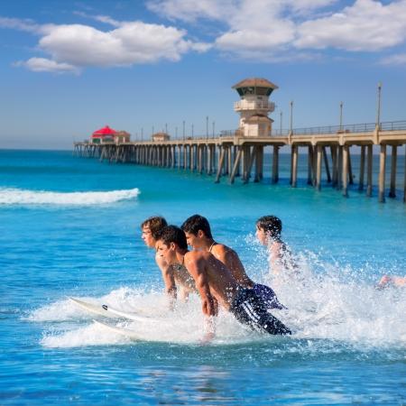 Teenager surfers surfing running jumping on surfboards at Huntinton beach pier California photo