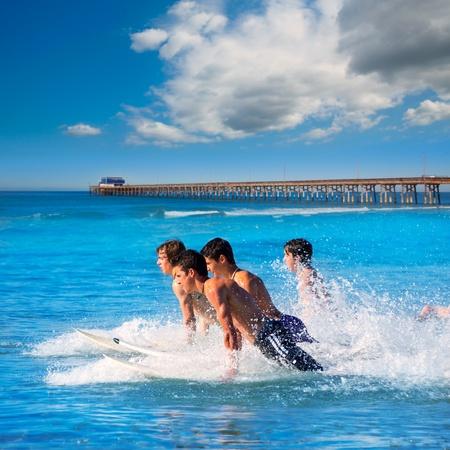 Teenager surfers surfing running jumping on surfboards at Newport pier beach California photo
