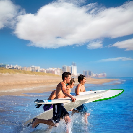 Teenager surfers surfing running jumping on surfboards at El Perello Cullera beach Spain photo