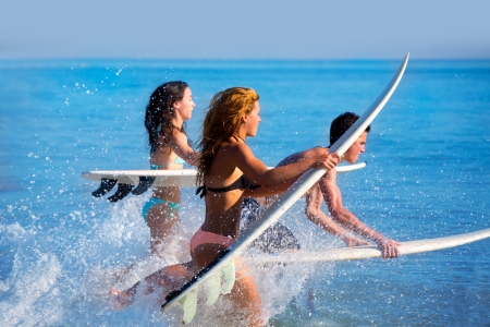 男の子と女の子の 10 代サーファーのビーチでサーフボードにジャンプを実行します。