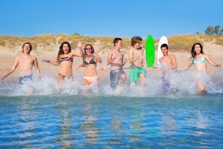 Teen surfers boys and girls group running happy to the beach splashing water photo