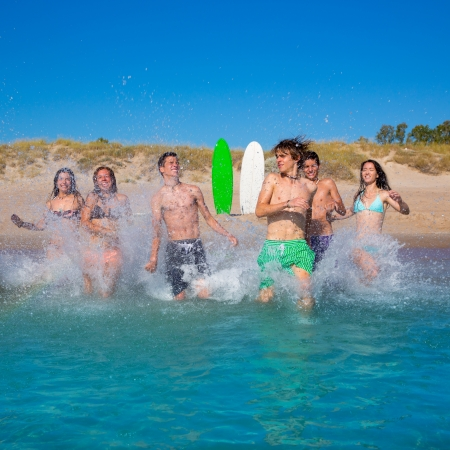 Teen surfers boys and girls group running happy to the beach splashing water photo