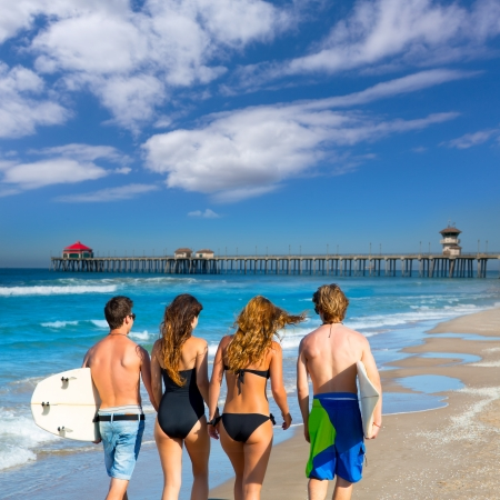 Teen surfers group of boys and girls walking rear view on Huntington beach California photo