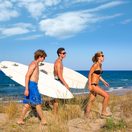 Surfer teen boys and girl group walking on dune way to beach on summer photo