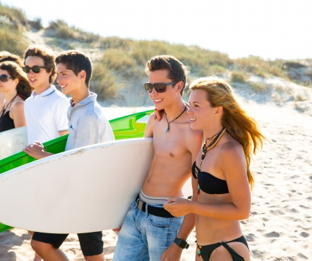 Surfer teen boys and girls group walking on beach sand photo