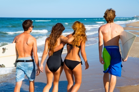 Teen surfers group of boys and girls walking rear view on beach photo