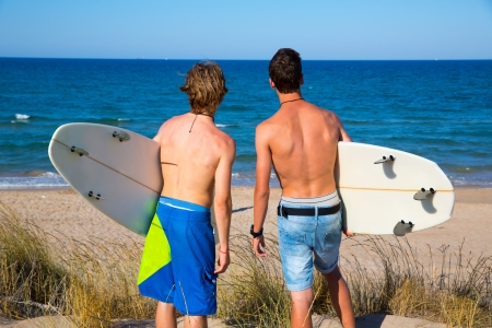Boys teen surfers rear back view looking at beach from uo dune photo