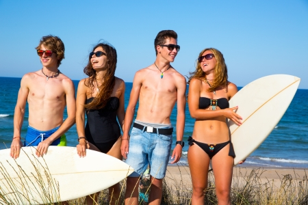 Boys and girls teen surfers happy smiling over dune beach in summer photo