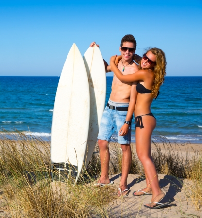 Teen surfers couple hug on the beach happy smiling photo