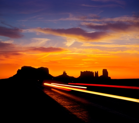 Sunrise on US 163 Scenic road to Monument Valley Park with car headlights Utah photo